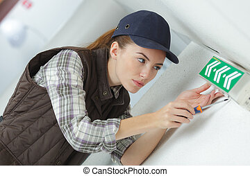 Young lady fitting emergency exit sign to wall