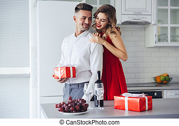 Young lady hug and looking at her man who holding present at home