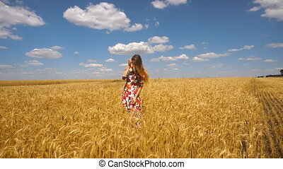 young lady in a dress standing in a wheat field