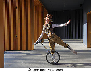 Young lady in a fantasy clothes with unicycle outdoors