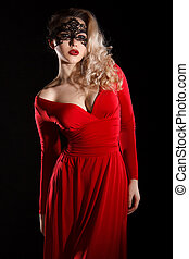 Young lady in a red evening dress and a black mask -...