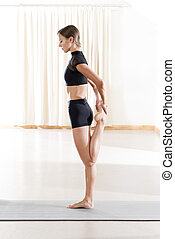 Young Lady in Black Crop Top Doing Thigh Stretching