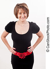 Young lady in black dress and red belt posing with her hands on waist