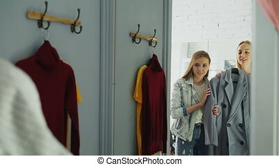 Young lady in casual clothes is trying coat in fitting room...