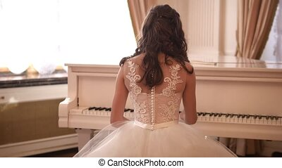 Young lady in evening dress in ballroom playing the piano -...