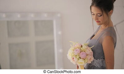 Young lady in gray dress with bouquet stands in front of mirror.