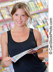 Young lady in newsagents holding a magazine