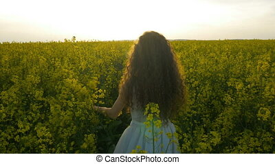 Young lady in white dress and curly hair strolling in...