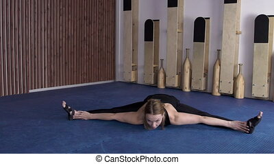 Young lady is doing middle sptits on yoga class.