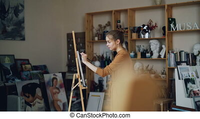 Young lady is focused on painting working in modern studio...
