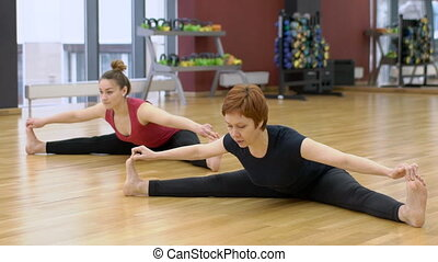 Young lady is having yoga class with her mature female trainer in modern gym, slow motion.
