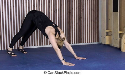 Young lady is having yoga training in modern gym with blue floor.
