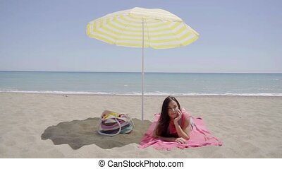 Young lady laying down on beach blanket - Single cute young...