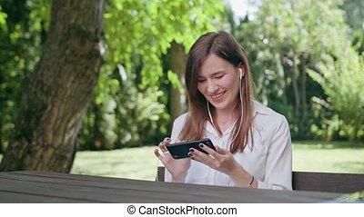 Young Lady Listening to Music in the Park