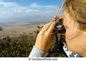 Young lady observing nature with binoculars