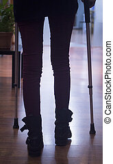 Young lady on crutches in hospital clinic silhouette