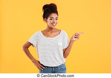 Young lady pointing at copy space and smiling isolated