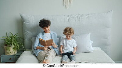 Young lady reading book while small son enjoying tablet...