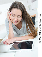 young lady relaxing and looking at tablet screen