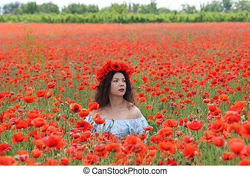 Young lady sitiing in poppies