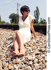 Young lady sitting at the railway