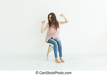 Young lady sitting on chair in white background with copy space