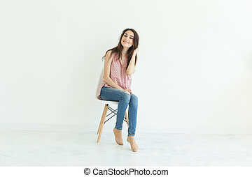 Young lady sitting on chair in white room with copy space