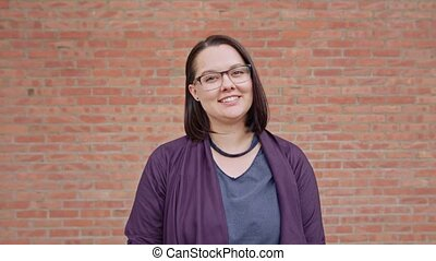 Young Lady Smiling against a Brick Wall Background