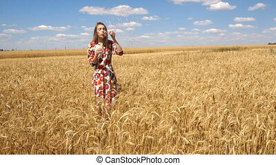 young lady standing in a wheat field against blue sky and inflates soap-bubbles in slow motion