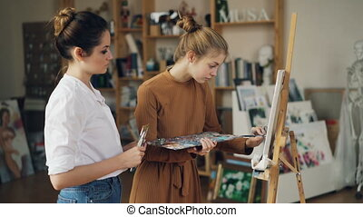 Young lady student is painting on canvas using oil paints...
