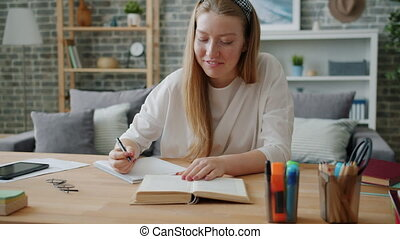 Young lady student writing in notebook at desk at home working at project