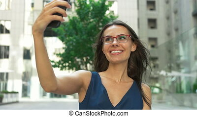 Young lady taking selfies in front of a business center.