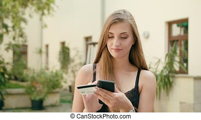 Young Lady Using a Phone and Holding Credit Card