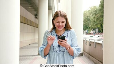 Young Lady Using a Phone in Town - A happy smiling lady...