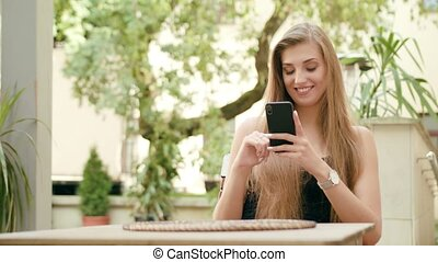 Young Lady Using a Phone in Town Sitting at the Table