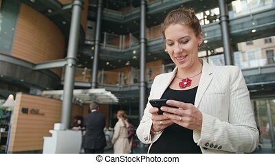 Young Lady Using a Smartphone in front of Building