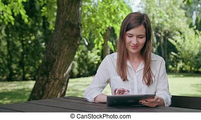 Young Lady Using an iPad in the Park - A young attractive...
