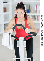 young lady using exercise machine at home
