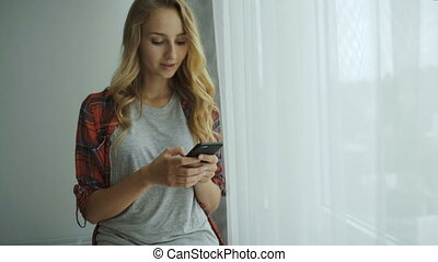 Young lady using her phone at home.