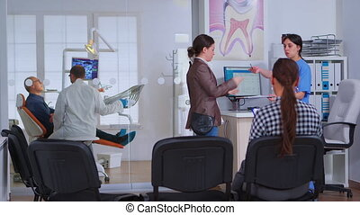 Young lady visiting stomatological clinic for teeth checking while dentistry doctor preparing old man for dental surgery in background. Patients sitting in crowded waiting room of orthodontist office