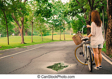 Young lady with bicycle on a road at park