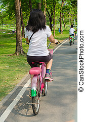 Young lady with bicycle on a road at park.