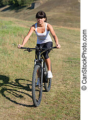 Young lady with bicycle on a spring meadow