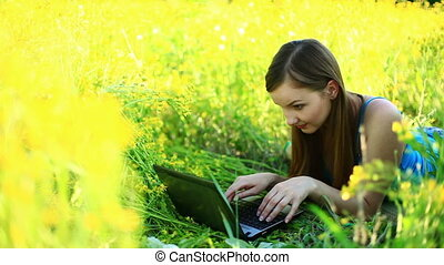 Young lady with laptop in the grass