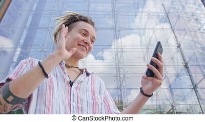 Young Lady with Modern Hairstyle Using Phone in Town - An...