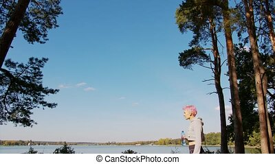 Young Lady with Pink Hair Jogging at the Lake - A young y...
