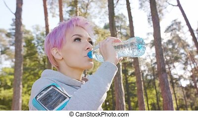 Young Lady with Pink Hair Jogging in the Forest - A young y...