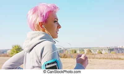 Young Lady with Pink Hair Jogging in the Suburbs - A young y...