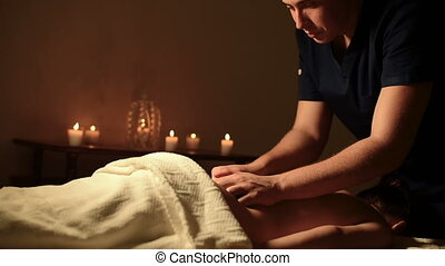Young large Caucasian male professional masseur doing spa massage to a girl in a dark office. medium close up