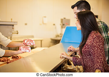 Young Latin couple buying meat